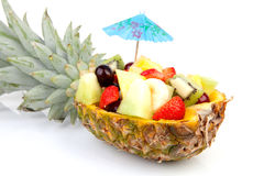 Pineapple filled with fresh summer fruits. Hollowed pineapple filled with fresh summer fruits over white background Stock Image