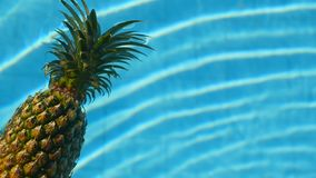 Pineapple floating in blue water in swimming pool. Healthy raw organic food. Juicy fruit. Exotic tropical background