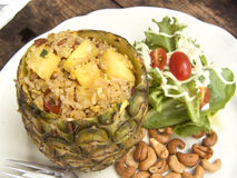 Pineapple fried rice. Delicious Asia - Asian eating Thai food. Pineapple fried rice stir with curry powder in pineapple shell served with salad, cashew nuts and royalty free stock photography