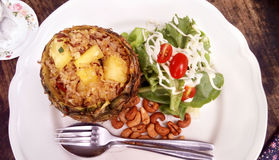 Pineapple fried rice. Delicious Asia - Asian eating Thai food. Pineapple fried rice stir with curry powder in pineapple shell served with salad, cashew nuts and stock photos