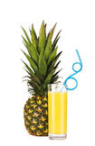 A pineapple fruit and a glass of pineapple juice with drinking straw. A whole pineapple fruit and a glass of pineapple juice with drinking straw isolated on Royalty Free Stock Photography