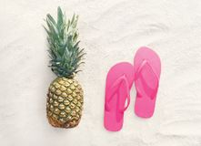 Pineapple fruit and pink flip flops on a beach white sand. Pineapple t and pink flip flops on a beach white sand background, top view royalty free stock images