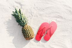 Pineapple fruit and red flip flops lying on beach white sand b Royalty Free Stock Photography
