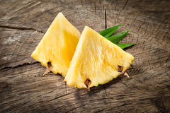 Pineapple. Fruit slices on wood background Stock Photos