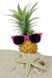 Pineapple fruit and sunglasses on sand. Pineapple fruit on the sand with sunglasses, starfish, and seashells. Isolated on white background Royalty Free Stock Photos