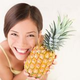 Pineapple fruit woman. Smiling healthy and joyful. Mixed-race Asian / Caucasian model on white background Royalty Free Stock Image