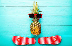 Pineapple with glasses and slippers on blue wooden background. Copy space and top view Stock Photography