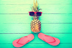 Pineapple with glasses and slippers on blue wooden background. Copy space and top view Stock Images
