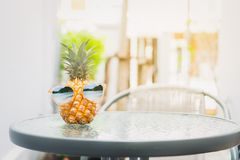 Pineapple with glasses is worn is placed on the table. Summer concept. stock photos