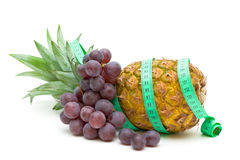 Pineapple, grapes and measuring tape Stock Images