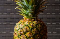 Pineapple on gray stripes background, vertical shot Royalty Free Stock Images