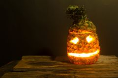 Pineapple Halloween jack. Lantern placed on the wooden floor and Black backdrop Royalty Free Stock Image
