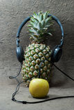 Pineapple with headphones and apple. Stock Photos