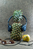 Pineapple with headphones and apple. Royalty Free Stock Photos