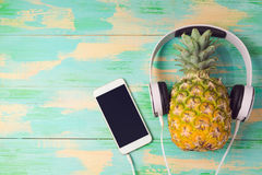 Pineapple with headphones and smart phone on wooden background. Tropical summer vacation and beach party concept. Royalty Free Stock Image