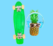 Pineapple with headphones sunglasses and skateboard Stock Photography