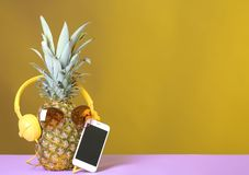 Pineapple with headphones, sunglasses and smartphone on table against color background. stock photos
