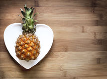 Pineapple on a heart-shaped plate. On wood royalty free stock photo