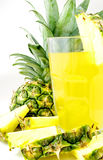 Pineapple juice. Tumbler with pineapple juice decorated with pineapple slices and a pineapple half with leaves Royalty Free Stock Images