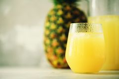Pineapple juice in glassware and whole pineapple fruit on gray background. Copy space, sunlight effect. Summer, holiday Royalty Free Stock Photo