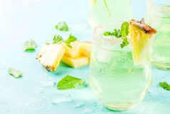 Pineapple juice margarita. Tropical drink, Pineapple juice margarita cocktail with fresh mint, light blue background copy space Royalty Free Stock Photos