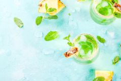 Pineapple juice margarita. Tropical drink, Pineapple juice margarita cocktail with fresh mint, light blue background copy space top view Stock Image