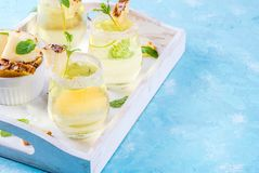 Pineapple juice margarita. Tropical drink,  Pineapple  juice margarita cocktail with fresh mint, light blue background, wooden tray, copy space Royalty Free Stock Image