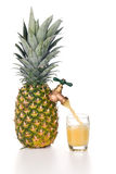Pineapple juice pouring into glass Stock Image