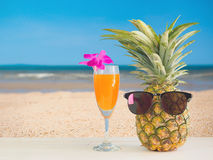 Pineapple juice with sea beach background. Pineapple juice on sea beach background in summer day with copy space Royalty Free Stock Photography