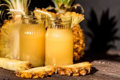 Pineapple juice and slice placed on a wooden table. Jars of pulpy fresh pineapple juice and pineapple slices placed on a wooden table. Summer drink concept Royalty Free Stock Images