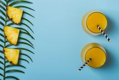 Pineapple juice or smoothies and pineapple slices on a blue background.  stock image