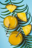 Pineapple juice or smoothies and pineapple slices on a blue background.  royalty free stock images