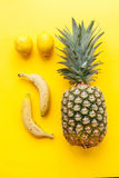Pineapple, lemons and bananas on yellow background Royalty Free Stock Photos