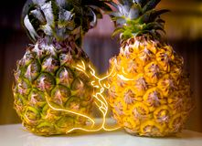 Pineapple lovers couple kissing in an intimate light. A boy and a girl. The concept of a tropical vacation. Royalty Free Stock Photos