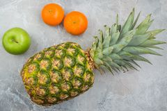 Pineapple, mandarines and apple. On the stone royalty free stock photography