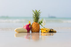 Pineapple, mango, dragon fruit and bananas on the beach. On blue sea background royalty free stock images