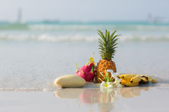 Pineapple, mango, dragon fruit and bananas on the beach. On blue sea background royalty free stock photo