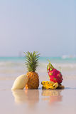 Pineapple, mango, dragon fruit and bananas on the beach. Pineapple, mango, dragon fruit and bananas  on the beach on blue sea background Stock Image
