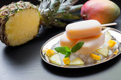 Pineapple mango sorbet ice cream popsicles. Exotic sorbet ice cream popsicles on silver plate with ice cubes chopped pineapple mango pieces, mint near half of Stock Photo