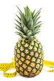Pineapple with measuring tape isolated over white. Royalty Free Stock Photo