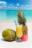 Pineapple, melon and a cocktail. On the sandy tropical beach Stock Photo
