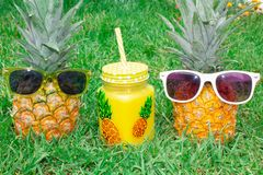 Pineapple mood. Two pineapple in sunglasses and a mug of juice. stock photos