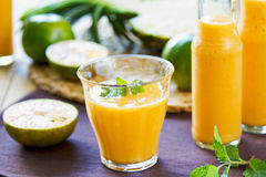 Pineapple with Orange and Mango smoothie. In a glass and bottles Stock Photography