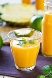 Pineapple with Orange and Mango smoothie. In a glass and bottles Royalty Free Stock Photos