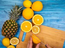 Pineapple, oranges resting on a wooden board stock photo