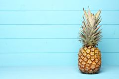Pineapple on a pastel blue wood background. Ripe pineapple on a pastel blue wooden background Royalty Free Stock Photo