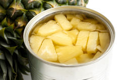 Pineapple pieces in tin on white. Pineapple pieces in tin on white next to pineapple Royalty Free Stock Photo