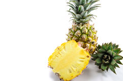Pineapple And Pieces. Two pineapples, one cut showing juicy insides Stock Photos