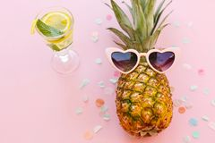 Pineapple in pink sunglasses and mojito cocktail drink on trendy. Pink paper background with confetti. summer vacation and party concept. space for text. summer Stock Photo