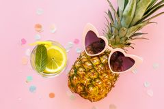 Pineapple in pink sunglasses and mojito cocktail drink on trendy. Pink paper background with confetti. flat lay. summer vacation and party concept. space for Royalty Free Stock Images